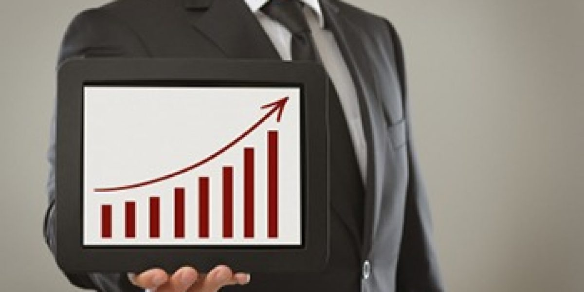 person in suit holding a tablet showing a bar chart with an increasing trendline