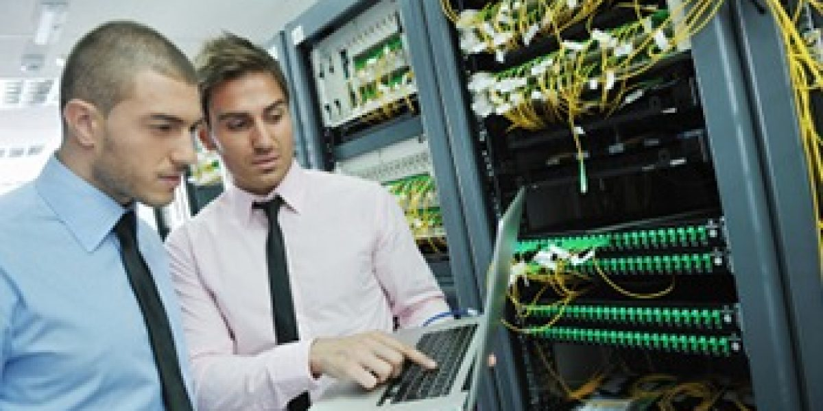 two people looking at laptop in front of a large server
